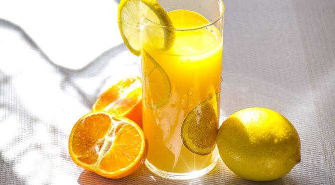prim plan cu un pahar de limonada pe marginea caruia e o lamaie si langa se afla o lamaie intreaga in partea dreapta si o portocala taiata pe jumatate in partea stand - reprezentare a Vitaminei C in limonada