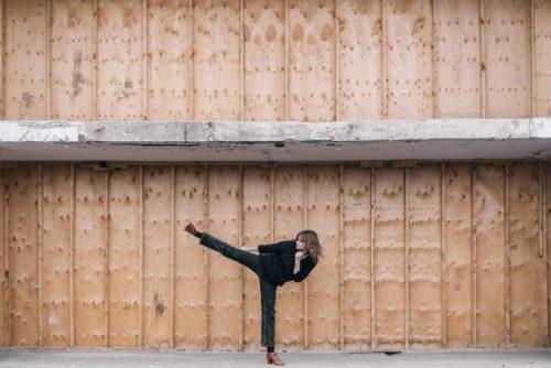 imagine a unei femei imbracata in negru care ridica piciorul intr-o pozitie de kick pe un fundal maro industrial