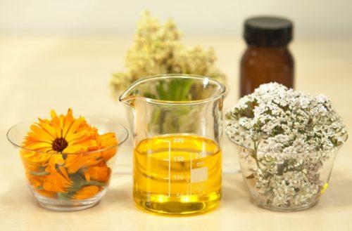 flori albe si portocalii in pahare de sticla